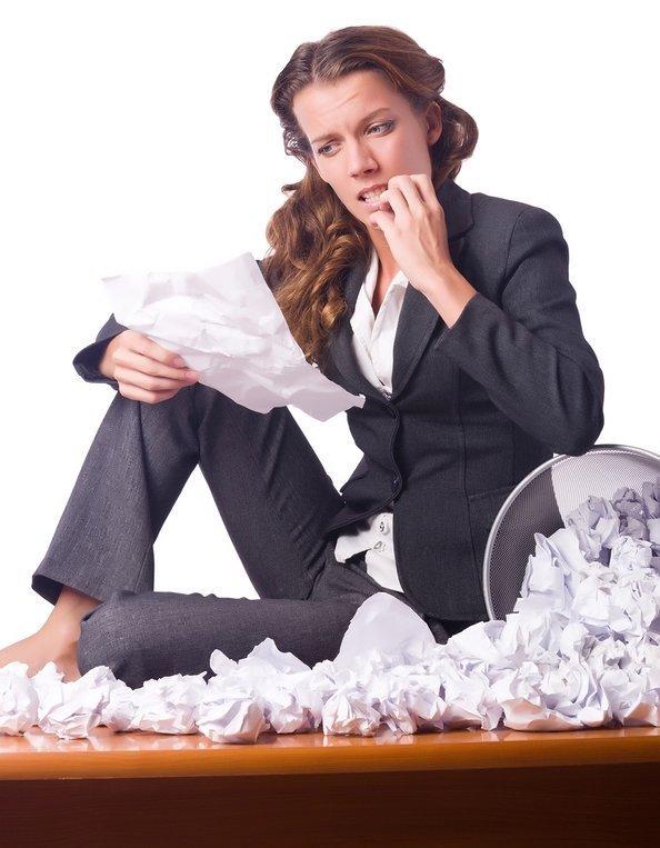 אישה בחליפה ומבט מתוסכל יושבת על שולחן מלא דפים מקומטים