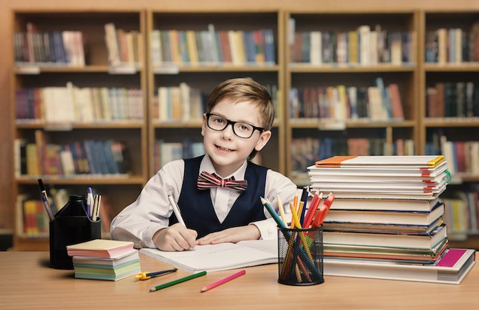 ילד עם משקפיים יושב כותב חשבונית מס וברקע ספרים