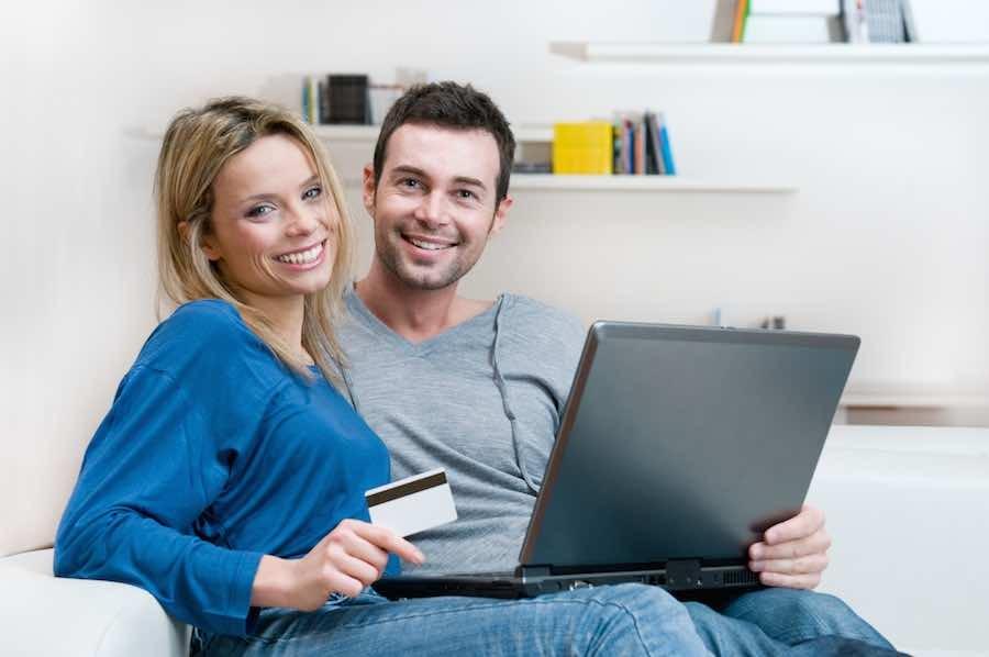 שני חברה יושבים עם מחשב וכרטיס אשראי על מנת לשלם לביטוח לאומי