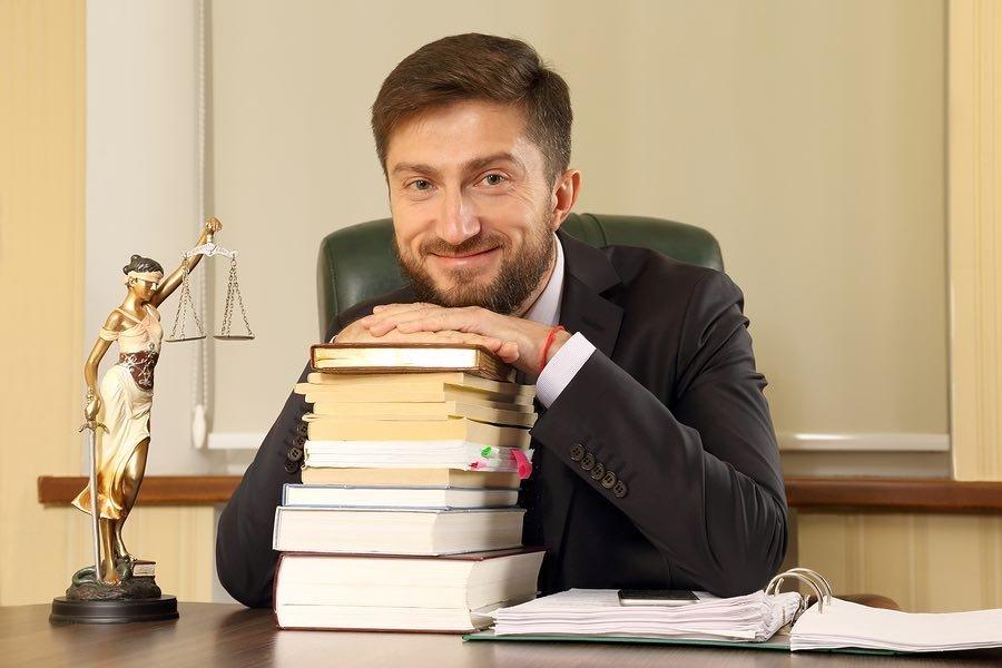 עורך דין מחייך נשען על ספרים