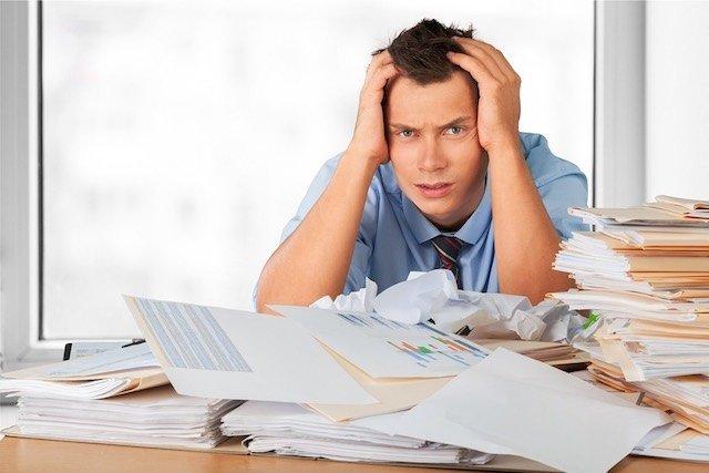 איש בפרצוף מיואש נשען על שולחן עמוס דפים