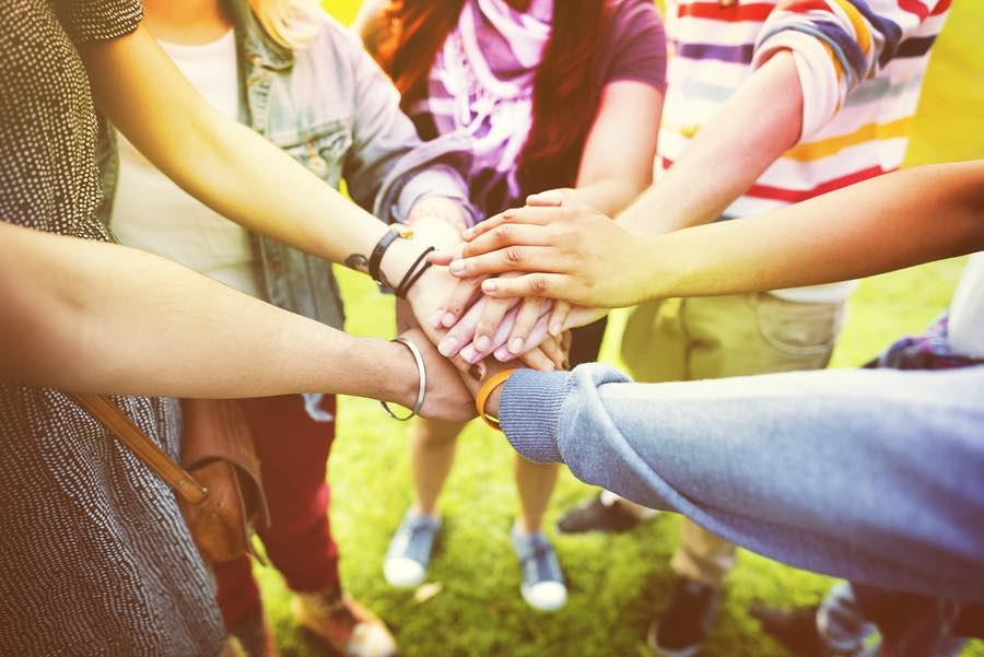 מעגל של אנשים שמים ידיים בערמה